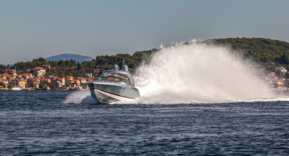 Fast boat rides on the sea and raises the wave behind.jpg