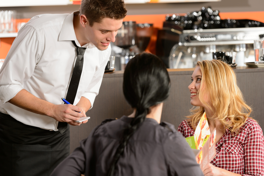 Waiter taking orders from young woman customer