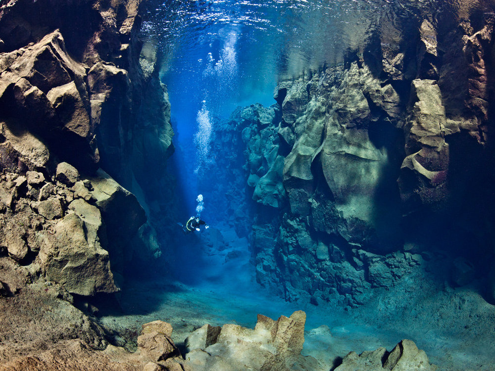 A diver swims between the North Amercian and Eurasian plate on the constructive plate boundary in Iceland [ Source ]