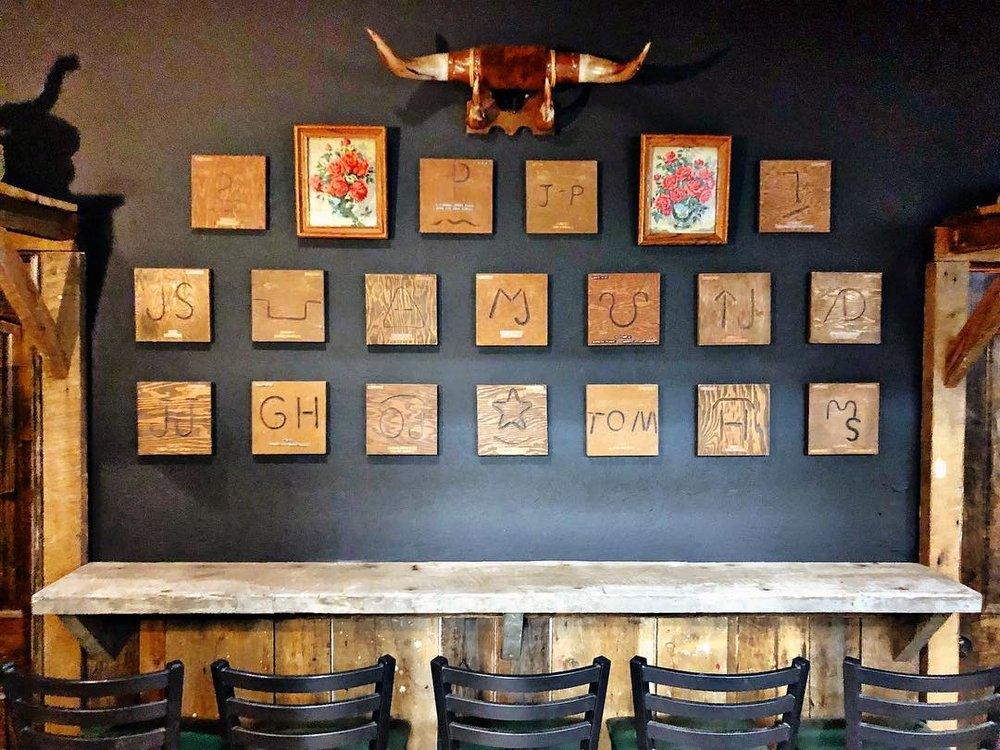 "I finished hanging the brands in the back room at the bar and got most of the ""ranch life"" decor and taxidermy up. It's so cool to have this collection as a part of the bar! There are 50 wooden plaques each branded with family cattle .jpg"