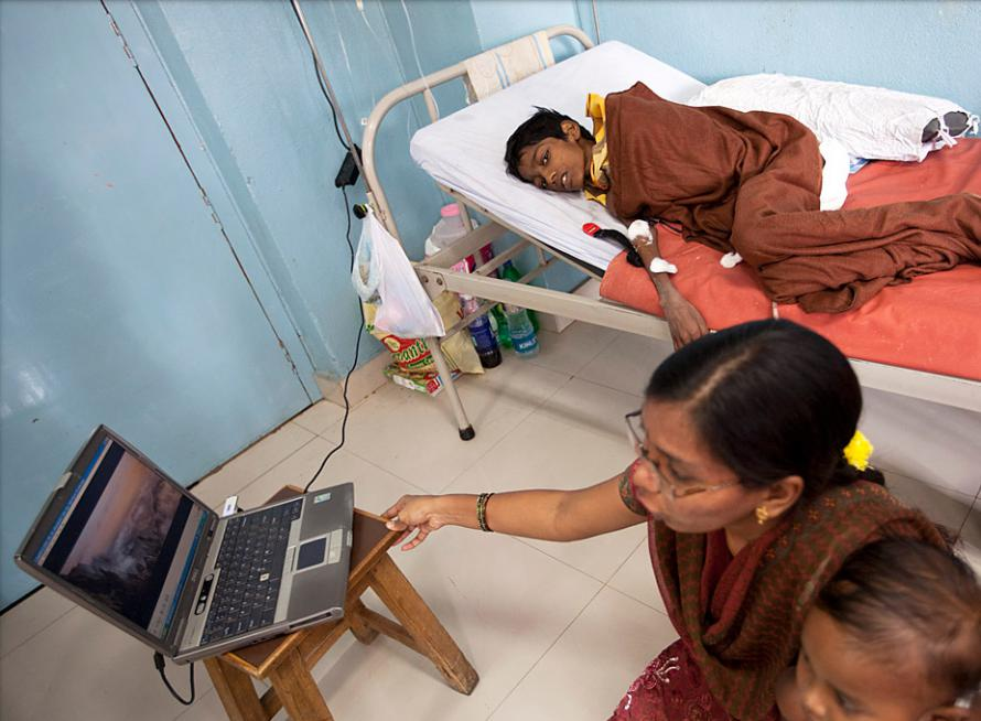 Social worker sets up a Telugu-language video on a Doctor's laptop in the paediatric ward.