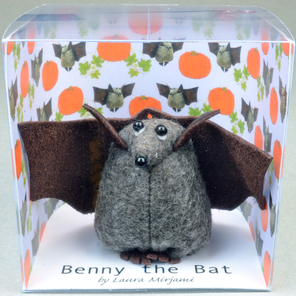 Handmade Benny the Bat felt paperweight with leather wings in its new packaging.