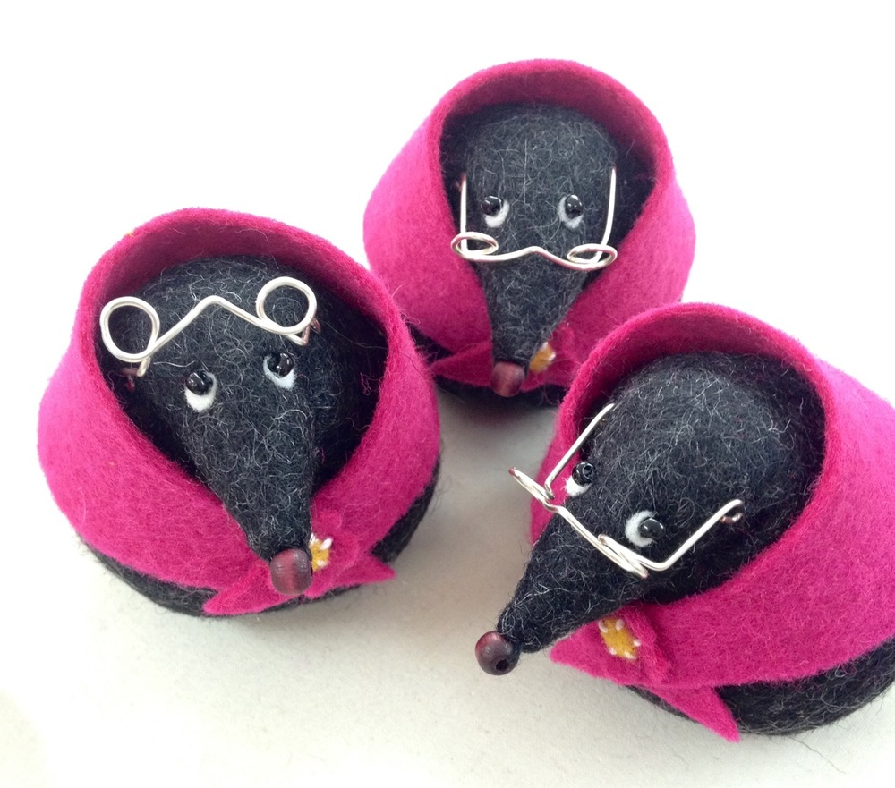 Three handmade felt mole paperweights.