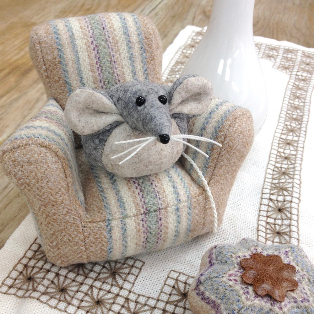 Marie the Mouse on a miniature tweed armchair with a matching footstool, handmade by Laura Mirjami | Mirjami Design.