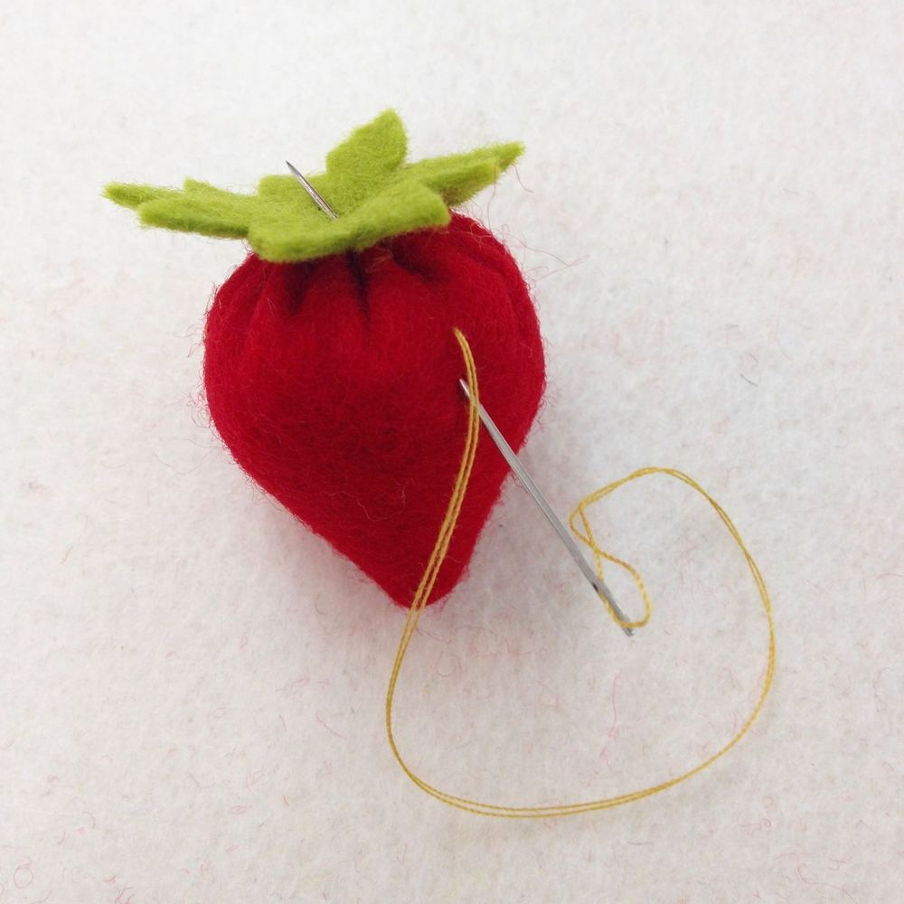 Go through to the body of the strawberry to create seeds and return through the leave a couple more times to attach it securely.
