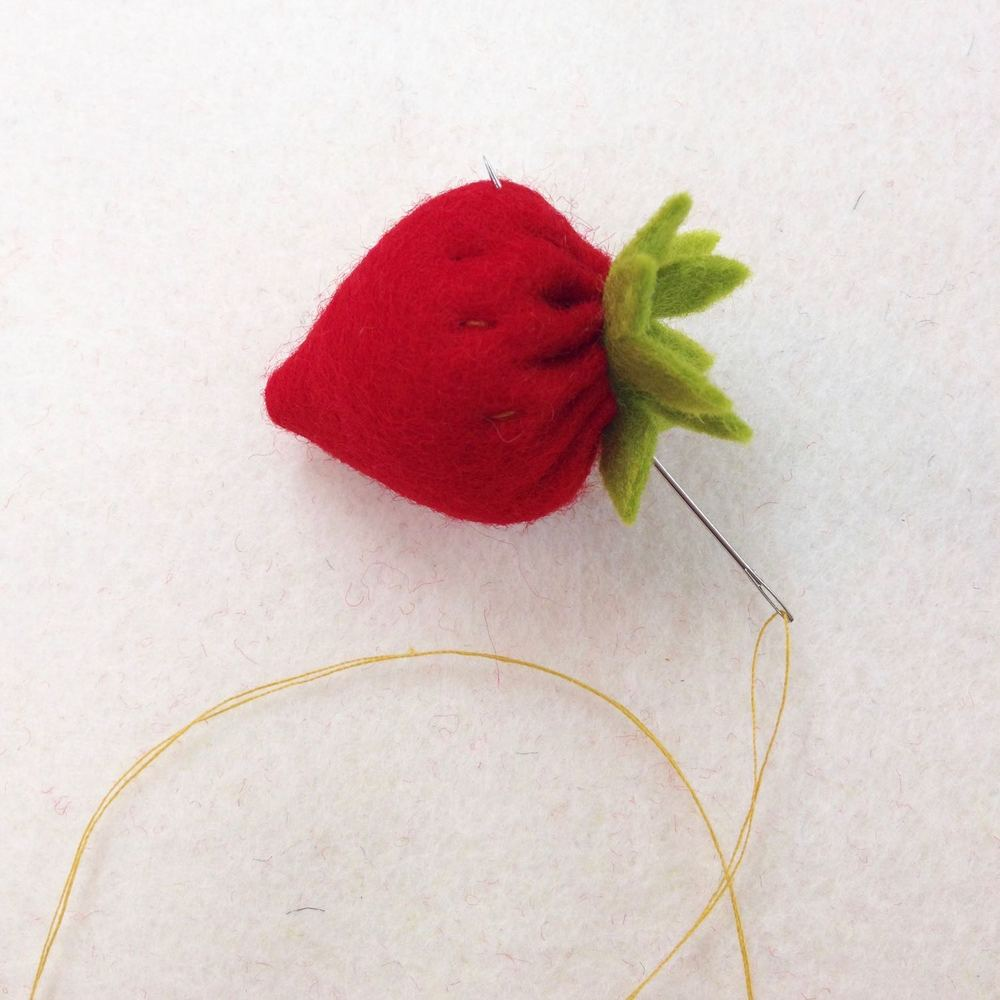 Once the leaf is on securely keep on going through the body of the strawberry creating seeds. If you pull your thread tightly you will create lovely little dips that makes it look even more like a real strawberry!