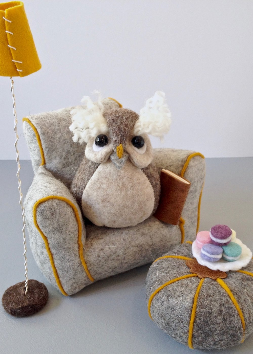 Felt miniature furniture | miniature yellow lamp | grey felt armchair and pumpkin pouffe | Bilberry Woods character Ollie the Owl sitting on a felt armchair with a leather notebook and felt macarons | Handmade by Laura Mirjami.jpg