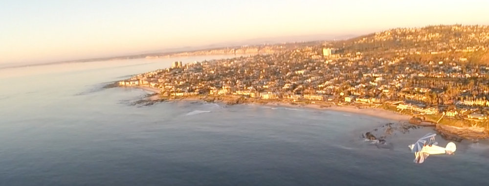 Flying north towards La Jolla Cove along the beach