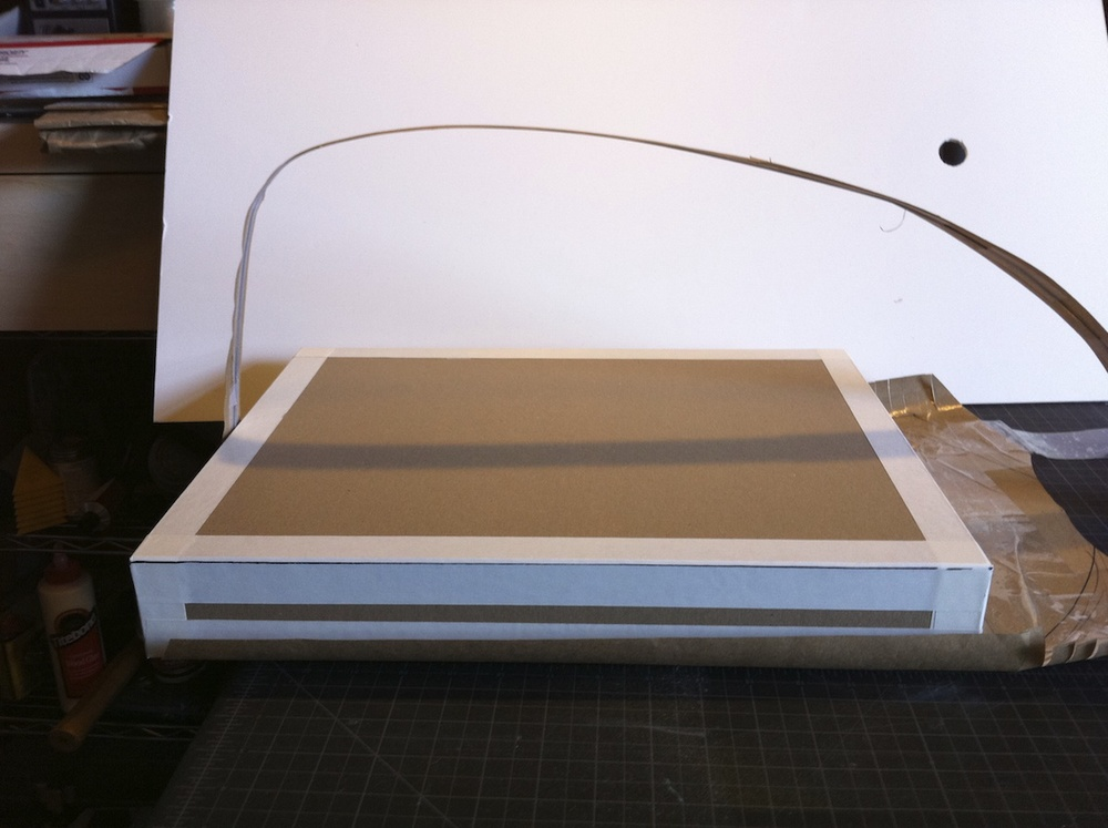 The box with the white tape around the edges is a stand in for the space required for the laptop and the drawing tablet.