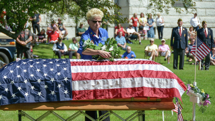 Laurie Asmus, president of the VFW auxiliary in Fargo, lays flowers on a ceremonial casket during a Memorial Day service at Riverside Cemetery in south Fargo on May 30, 2016. Rick Abbott / The Forum