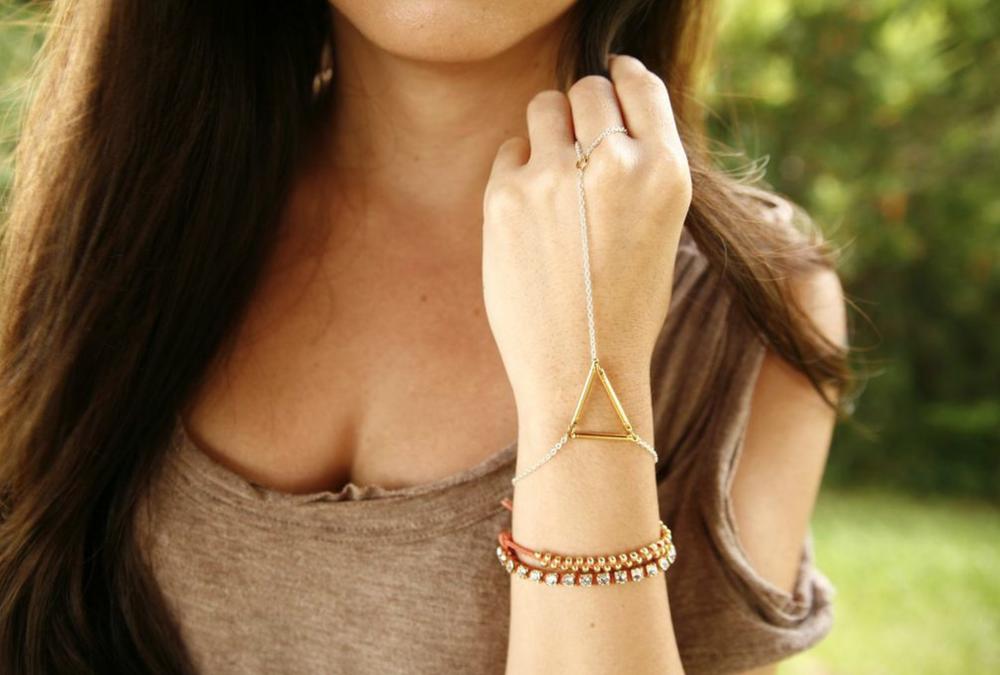 Summer is wearing the Geo Wrist to Ring Bracelet in Two-Tone, the Lovewrap in Orange and the Anwar Bracelet in Teal.