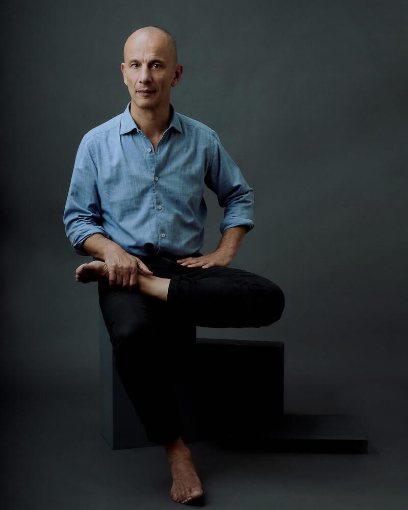 Portrait du chiropraticien Steve Haines. Cette image est une série d'ateliers pour les professeurs de yoga. La jambe parallèle au sol rappelle certaines postures de yoga. Ceci est accentué par la boîte «applebox» qui est parallèle en dessous de la jambe.