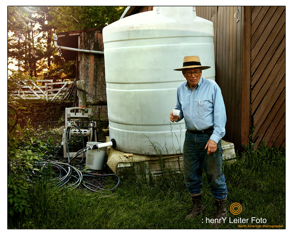 Farmer John Hohmann, M.D. stands in front of one of his many rain collection cisterns and discusses the benefits of chemical-free farming.