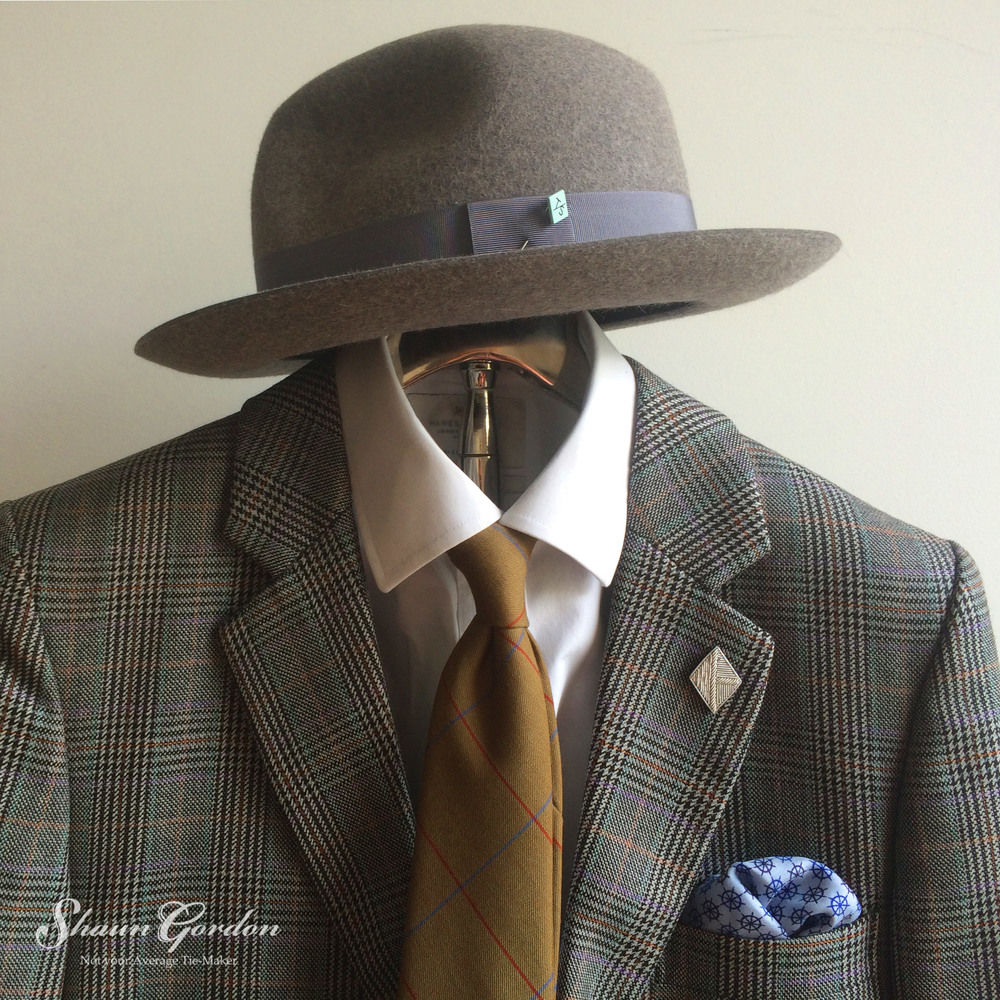 Prince Of Wales Check Experiment: The eccentric mixture of different patterns are certainly held together with the solid grey tone of the hat.