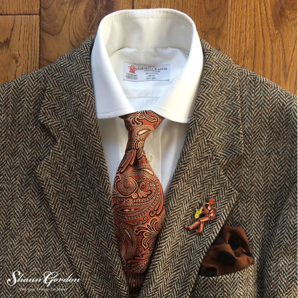 The Montgomery paisley tie is for the bold and adventurous! The mixture of Pattern and bold colour is not only playful, but in fairness, the range of hues are complimentary because the copper orange acts as an accent to the malt Brown of the tweed jacket.