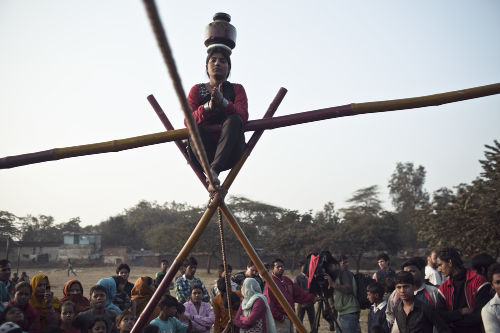 Maya Pawar prepares to stand up on the tightrope, as children from the colony gather to watch.