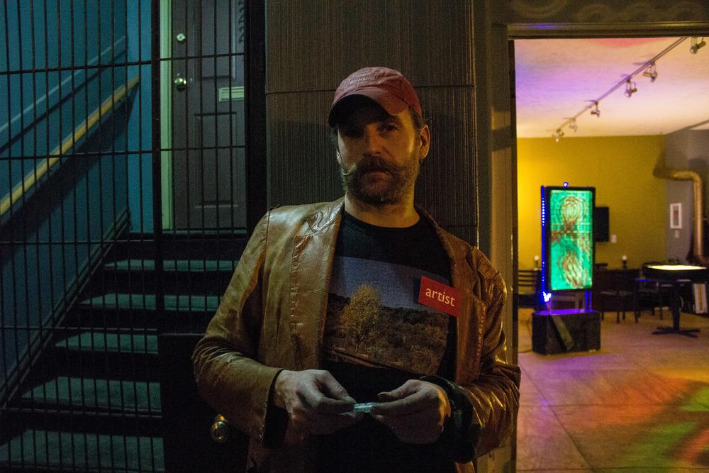 Artist Aaron Lee Van Wyk with his installation in the background.