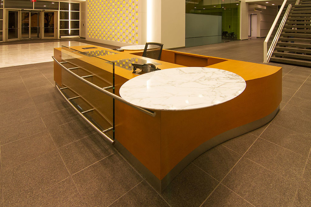 The new reception desk was fabricated in wood, white Carrera Marble transaction tops, and glass screen panel mounted with stainless steel rails.  Note that all security devices including monitors are fully recessed with glass covers for protection.  The desk is sized to seat two and positioned to view both the front, back and both side entries.