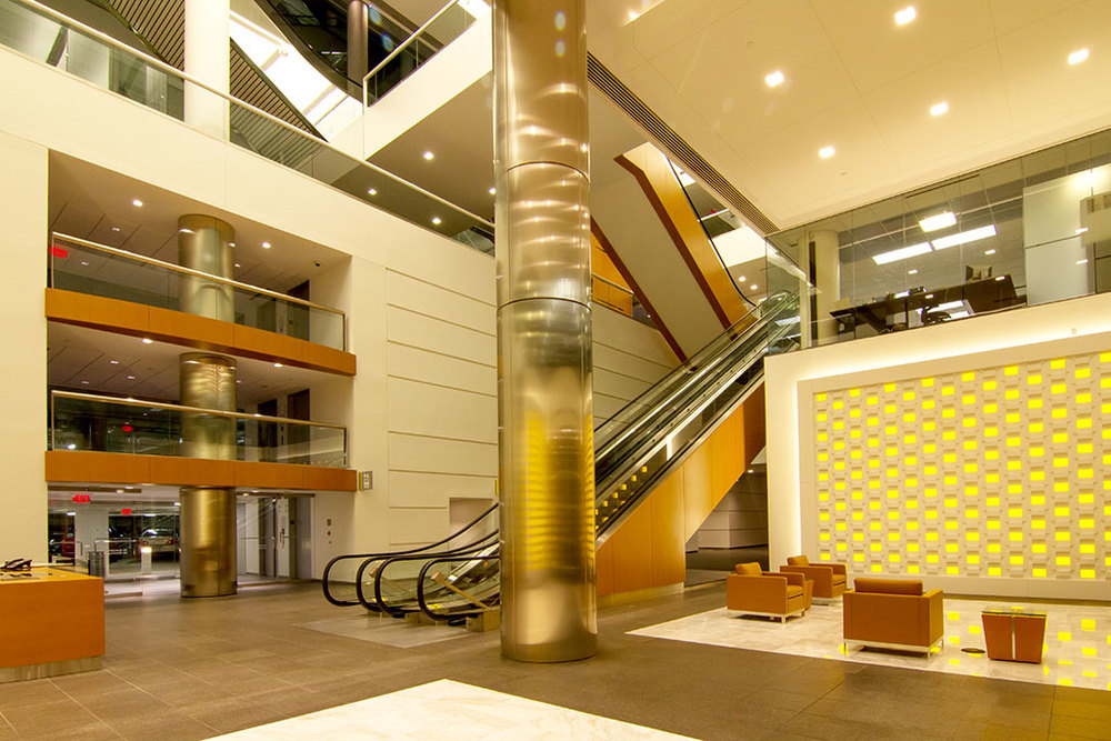 The main reception features new wood balcony spandrels, wood escalator siding and the Modular Arts sculpted feature wall with illuminated yellow accent fabric panels behind.  Furniture was specified in a caramel leather to tie back to the warm wood tones.
