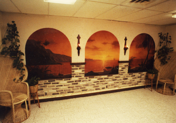 "In 1977 after graduating high school and prior to working as an architectural/interior designer Brad worked for a short time at a local Target store in maintenance department. Brad couldn't stand all the bland walls in the break room nor could the other employees, so Brad whipped out this mural painting a tropical sunset scene requisitioning paint department and some fake ""Z"" brick, chairs and plants from the Home & Garden department."