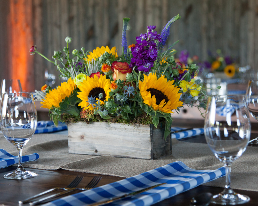 "We recently had a great opportunity to work with a local company in Park City for a ""ho-down"" event located at the beautiful Blue Sky Ranch in Wanship, UT. RMC (Rocky Mountain Connection) organized and designed this Western themed party. The elements were so bright, vibrant and whimsical. Some of our favorite details were the blue checkered napkins and of course the mechanical bull for guests to ride and  try to conquer. A huge thank you to Kati Price and her team at RMC for allowing everyone at Lilac Floral to collaborate together for such a fun and successful event. Photos Courtesy of Marc Estabrook"