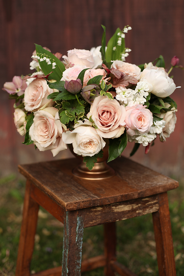 Blush centerpiece with peonies, lily of the valley, roses, garden roses, hellebores and stock, by Cincinnati florist Floral Verde LLC.