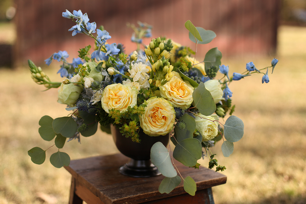 Centerpiece with bella donna delphinium, eryngium, round leaf eucalyptus, dusty miller, green trachelium, bupleurum, Yellow Finesse roses, Lime Piano garden roses and yellow ornithogalum in a footed bowl, by Cincinnati wedding florist Floral Verde LLC.