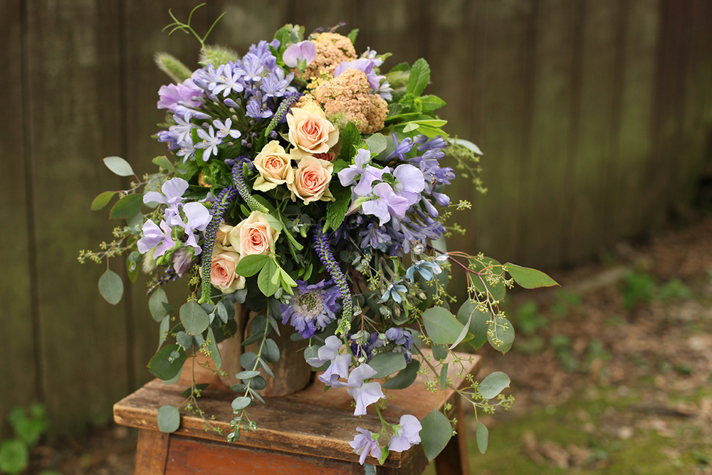 Cascading bouquet with peach yarrow, Chablis spray roses, lavender sweet pea, fresh lavender, blue veronica, blue scabiosa, tweedia, gunnii eucalyptus, seeded eucalyptus, bunny tail grass, mint , baptisa and blue agapanthus, by Cincinnati wedding florist Floral Verde LLC.