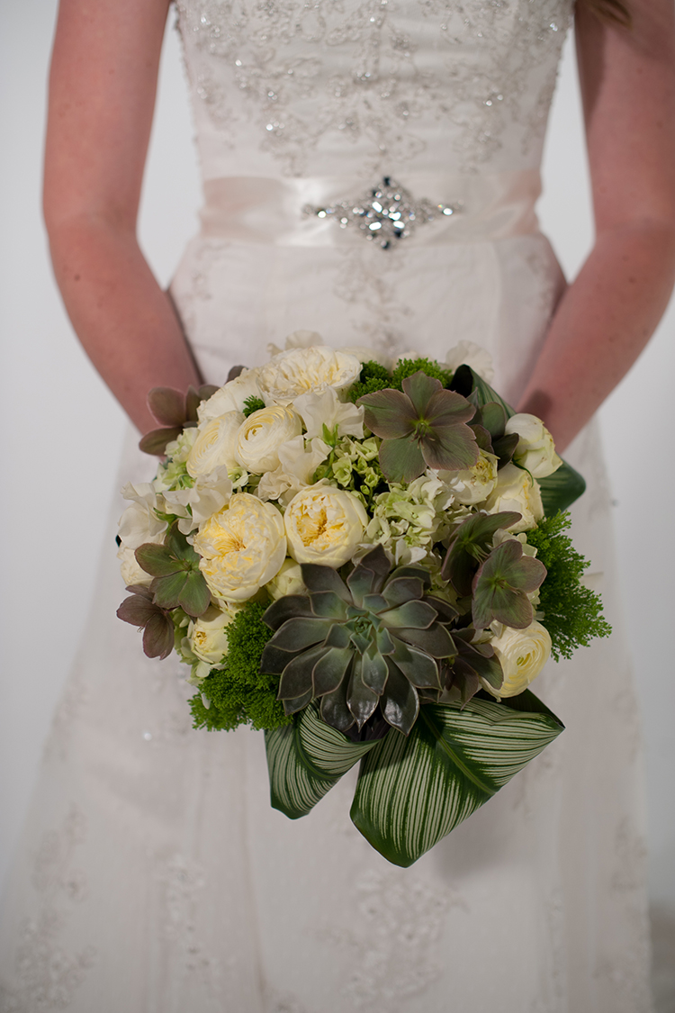 Hand-tied bridal bouquet by Floral Verde, in Cincinnati, Ohio, with echeveria 'Mensa', pink/beige hellebores, calathea, jade trachelium, green hydrangea, Antique Romantica garden spray roses, cream ranunculus, and ivory Japanese sweet peas. Photo by  The R2 Studio .