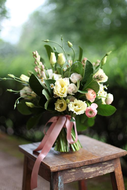 Fragrant bridal bouquet with cream lisianthius, chamomile, White Majolica spray roses, tuberose, peach ranunculus and magnolia foliage. By Cincinnati wedding florist Floral Verde LLC.