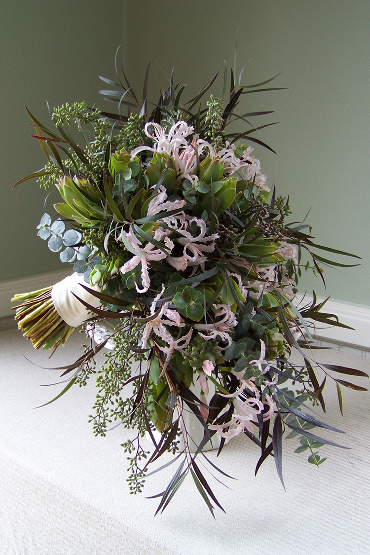 Cascade bouquet with blush nerine lilies, agonis, baby blue eucalyptus, seeded eucalyptus and green leucadendron. By Cincinnati wedding florist Floral Verde LLC.