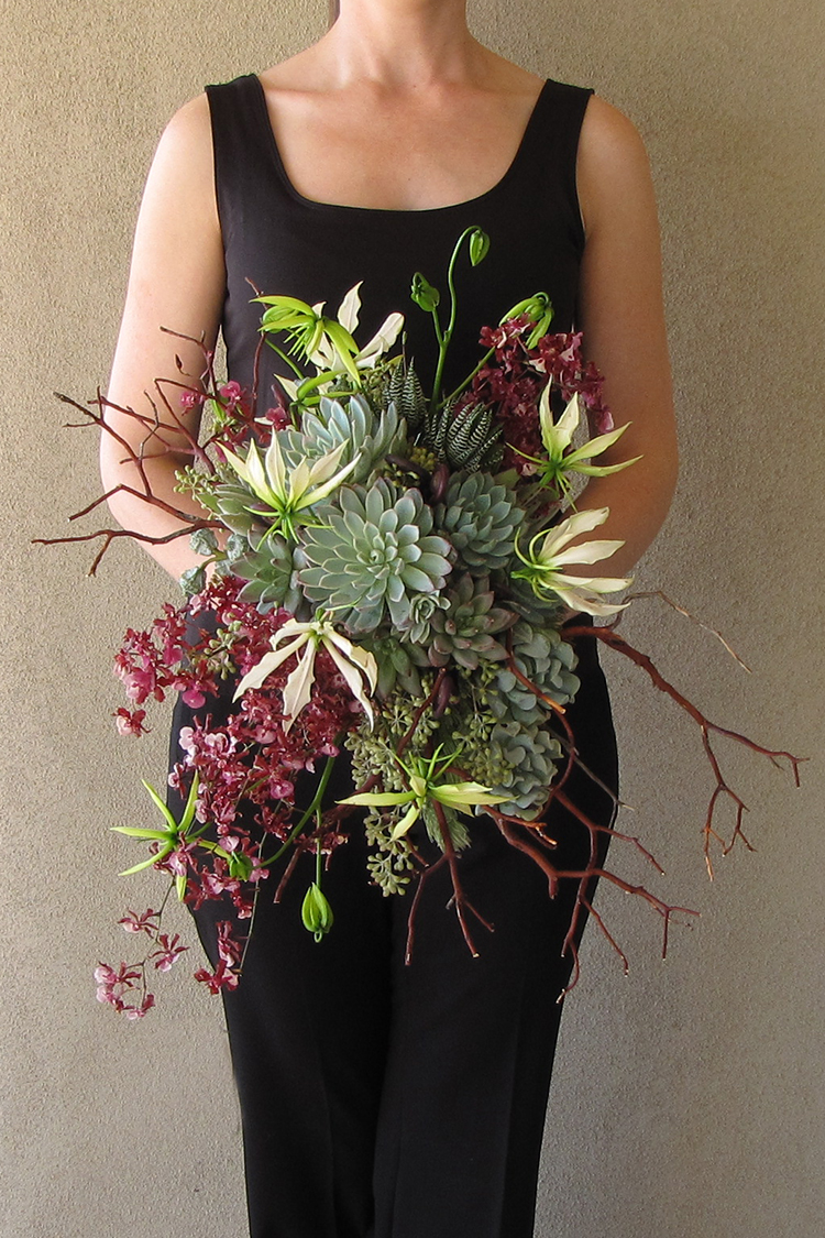 Cascading bridal bouquet with manzanita branches, uluhe fern curls, Oncidium Sharry Baby, white gloriosa lilies, Graptoveria 'Bella', Pachyveria glauca 'Little Jewel', Kalanchoe tomentosa, Echeveria 'Mazarine', Echeveria 'Violet Queen', Echeveria runyonii 'Topsy Turvy',eucalyptus bells, seeded eucalyptus, wooley bush, and Haworthia fasciata, by Cincinnati wedding florist Floral Verde LLC.