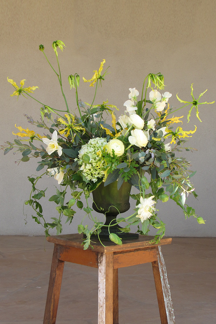 Garden centerpiece by Cincinnati wedding florist Floral Verde LLC.  Centerpiece contains ivory sweet peas, ivory ranunculus, ivory daffodils, yellow gloriosa lily, green hydrangea, scented geranium, gunnii eucalyptus and passion vine, arranged in a vintage green urn.