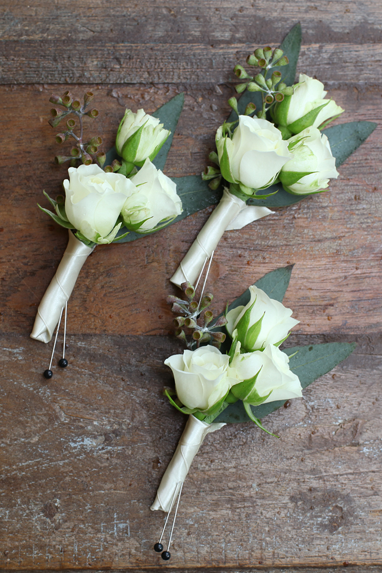 Boutonnieres with Snow Flake spray roses and seeded eucalyptus. By Cincinnati wedding florist Floral Verde.