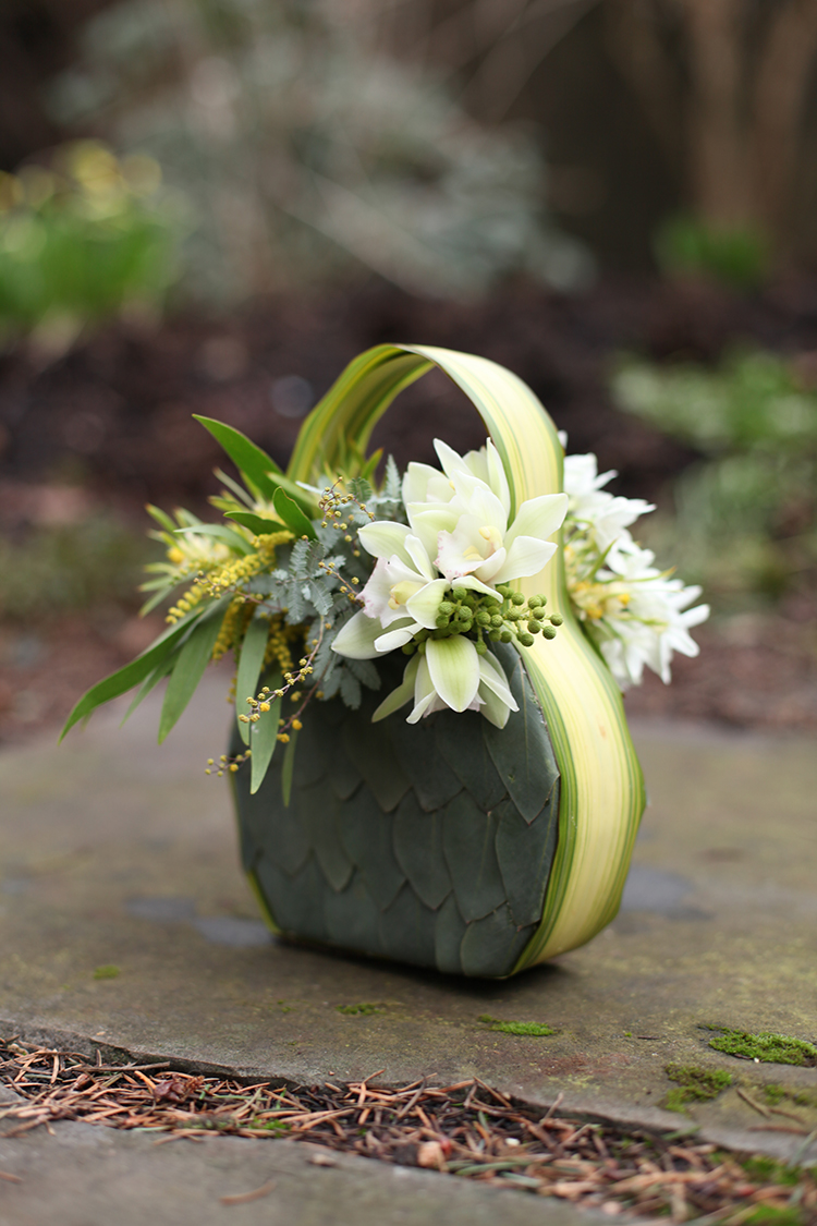 Floral purse with eucalyptus foliage, variegated flax, mini leucadenron, flowering acacia, berzillia, mini cymbidiums, narcissus and succulents. By Cincinnati wedding florist Floral Verde.