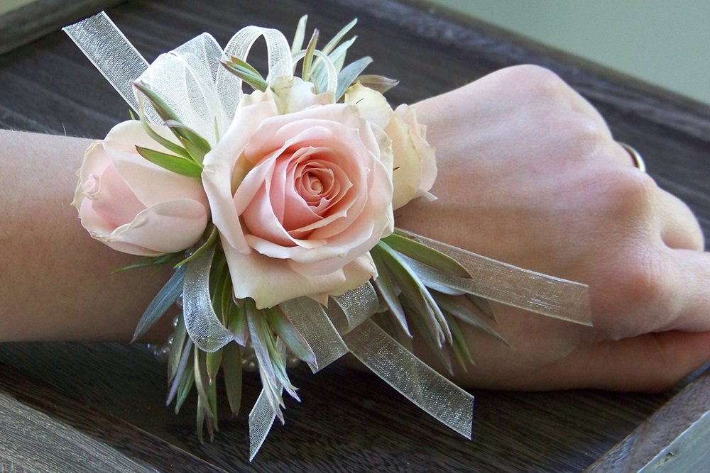 Wrist corsage with Star Blush spray roses, green leucadendron and ivory chiffon ribbon on an ivory pearl bracelet. By Cincinnati wedding florist Floral Verde LLC.