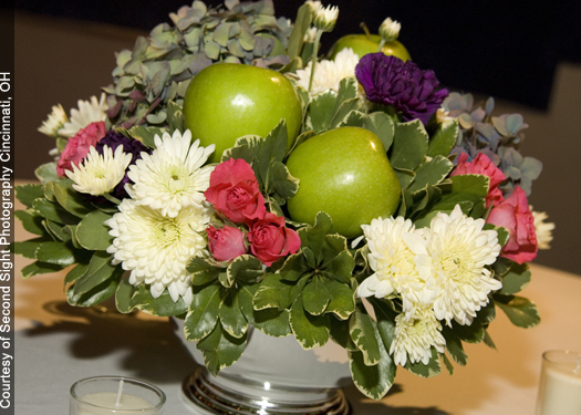 centerpiece with Florigene Moonvista carnations, antique blue-pink hydrangea, Twinkle Bride spray roses, green apples, Polaris cushion pomps and a variegated pittosporum in a silver Revere bowl