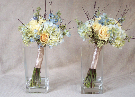 hand tied bridesmaids bouquets with Cream Prophyta roses, pale blue hydrangea, light blue delphinium, seeded eucalyptus, and bamboo
