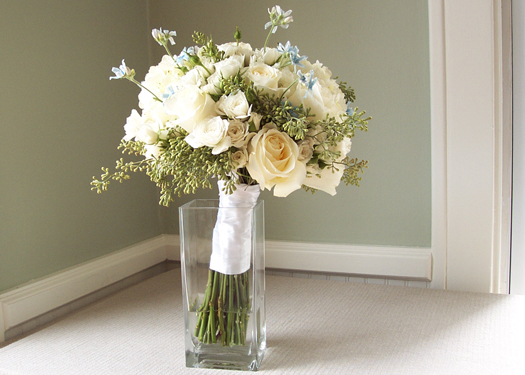 hand tied bridal bouquet with Blizzard roses, white spray roses, white hydrangea, seeded eucalyptus and blue tweedia
