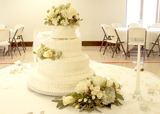 wedding cake with Blizzard roses, white spray roses, pale blue hydrangea, and seeded eucalyptus