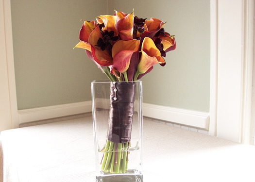 hand tied fall bridal bouquet with mango mini callas, chocolate cosmos, and a chocolate satin stem wrap