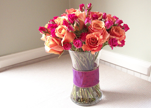 a wide band of ribbon pulls the arrangement of Milva roses and hot pink spray roses together