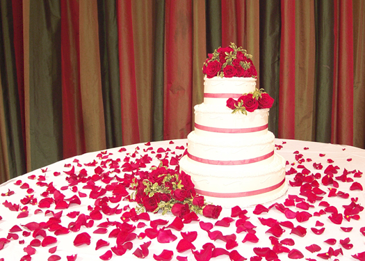 wedding cake adorned with red Freedom roses and Scarlet spray roses