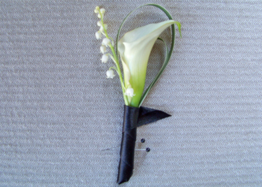 groomsmen boutonniere with a white mini calla, lily of the valley and variegated lily grass