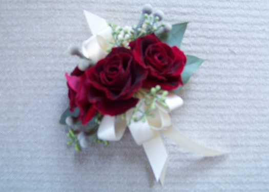 corsage with Black Beauty sweetheart roses, seeded eucalyptus and silver brunia