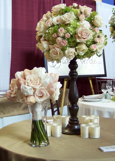 centerpiece on a 20 inch turned wood candle stand, containing hydrangea, bupleurum, Sahara roses, Champagne sweetheart roses and Peach Vision spray roses