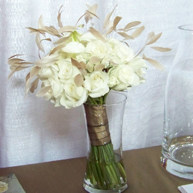 glamorous bouquet containing Escimo roses, Viviane spray roses, white mini callas, and beige stripped coque feathers