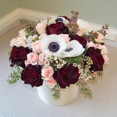 one dozen Black Baccara roses, Peach Vision spray roses, anemone, wax flower, and seeded eucalyptus in a six inch cylinder vase wrapped with champagne silk