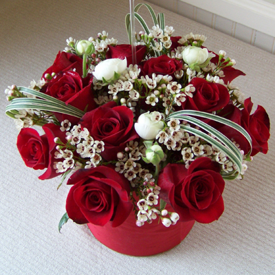 one dozen red Freedom roses, ranunculus, wax flower, and variegated lily grass in a six inch cylinder vase wrapped with red silk
