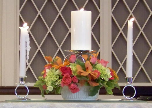 The unity candle arrangement contained Kiko roses, Twinkle Bride spray roses, orange vanda orchids, green hydrangea and scented geranium